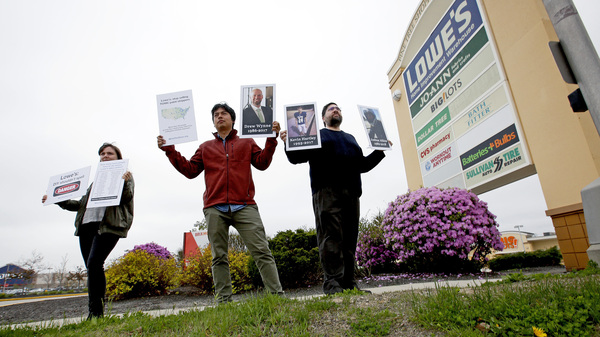 Protestors holding pictures of people who died from use of paint removers, including Drew Wynne, protest outside a Portland, Maine, Lowe