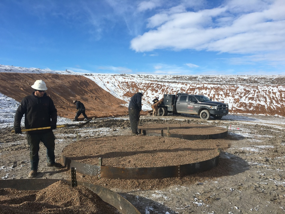 Workers at a Wold Energy Partners well pad in Wyoming place gravel where oil tanks will soon stand. A spike in drilling in the state is getting a boost from new lease sales on public land. (Cooper McKim/Wyoming Public Media)