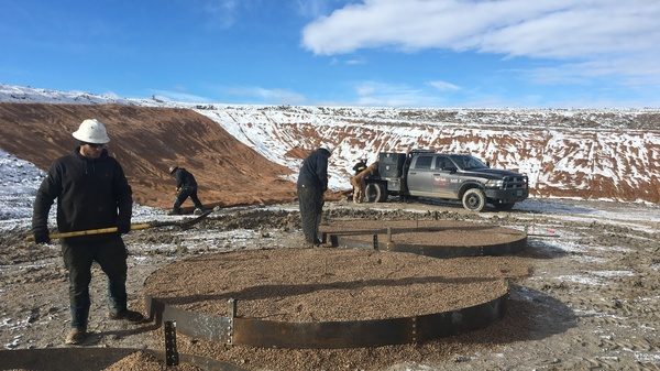 Workers at a Wold Energy Partners well pad in Wyoming place gravel where oil tanks will soon stand. A spike in drilling in the state is getting a boost from new lease sales on public land.