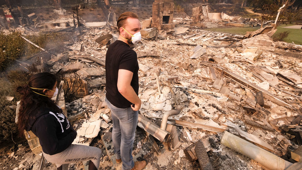 A California man and his girlfriend return to his burned out home in Malibu on Saturday.