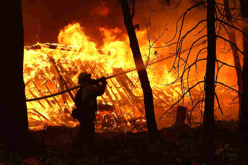 A firefighter sprays water on a home next to a burning home as the Camp Fire moves through the area in Magalia, California.