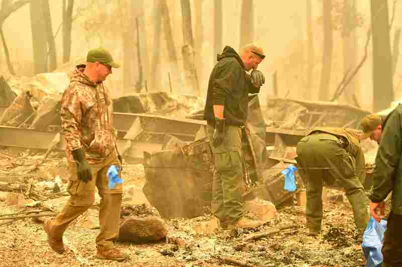 Yuba and Butte County Sheriff officers react as they discover a body at a burned out residence after the Camp fire tore through the area in Paradise, California.