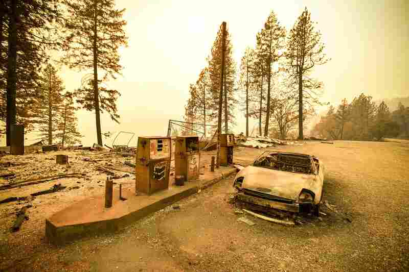 As the Camp Fire burns nearby, a scorched car rests by gas pumps on Sunday near Pulga, Calif., a community located in Northern California's Butte County.