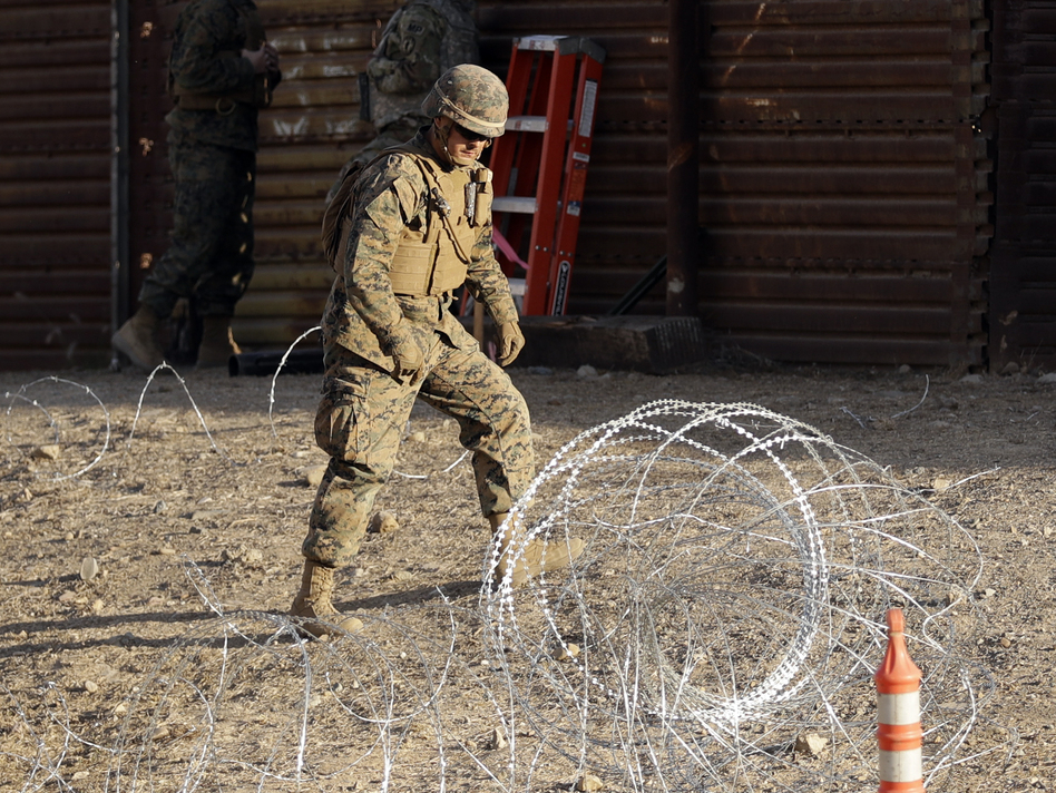 A Marine uses concertina wire to fortify the border separating Tijuana, Mexico, and San Diego, near the San Ysidro Port of Entry. (Gregory Bull/AP)
