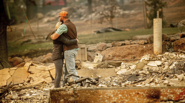 Chris and Nancy Brown embrace while searching through the remains of their home, leveled by the Camp Fire in Paradise, Calif.
