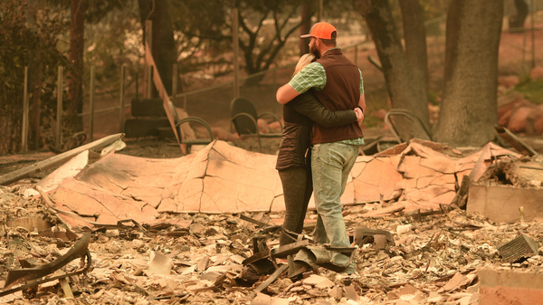 Chris and Nancy Brown embrace while looking over the remains of their burned residence after the Camp Fire tore through Paradise, Calif.
