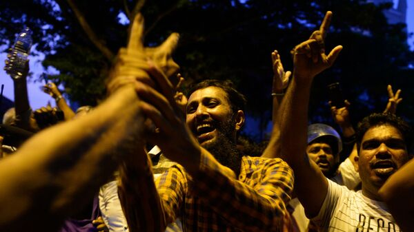 Supporters of ousted Sri Lankan Prime Minister Ranil Wickremesinghe shout in joy Tuesday outside the Supreme Court building in the capital, Colombo.
