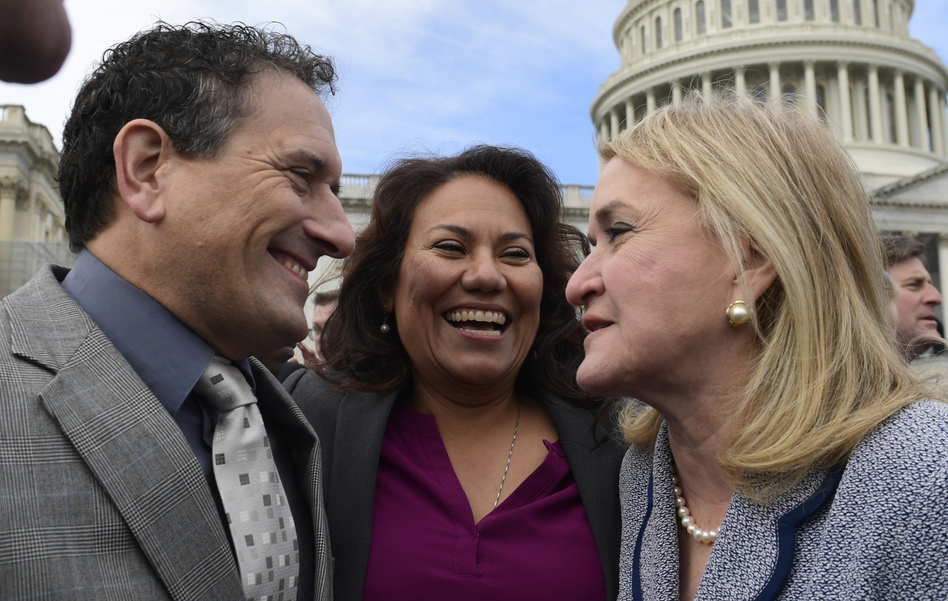 Rep.-elect Andy Levin, D-Mich. (left); Rep.-elect Veronica Escobar, D-Texas (center); and Rep.-elect Sylvia Garcia, D-Texas, talk following a photo of the incoming members of Congress on Capitol Hill on Wednesday. (Susan Walsh/AP)