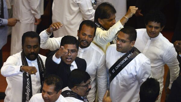 Members of the Sri Lankan parliament shout slogans in support of former Prime Minister Ranil Wickremesinghe during a parliament session in Colombo on Wednesday that ousted his successor, Mahinda Rajapaksa.