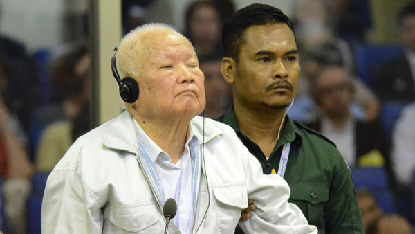 Khieu Samphan, left, former Khmer Rouge head of state, stands at the dock in a court room during a hearing at the U.N.-backed war crimes tribunal in Phnom Penh, Cambodia, on Friday.