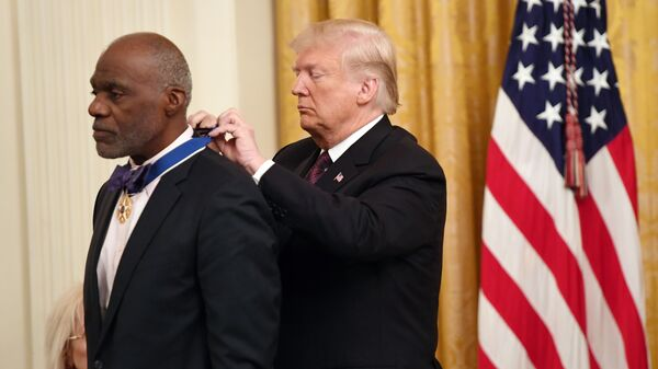 President Trump awards the Presidential Medal of Freedom to American Football hall-of-famer Alan Page at the White House on Friday.