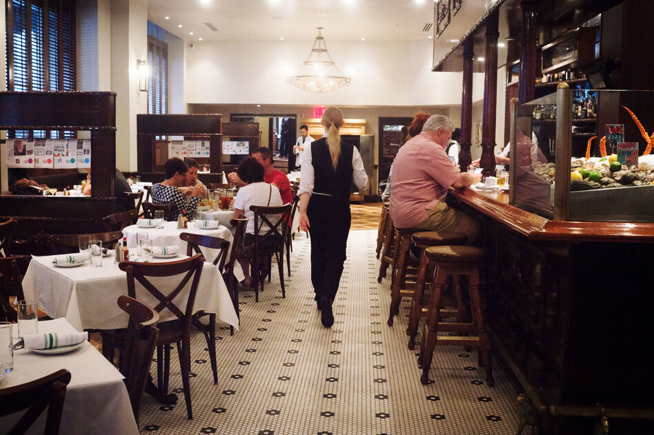 A member of the staff walks through Luke, one of the restaurants still owned by John Besh, on St. Charles Avenue in New Orleans. (Emily Kask for NPR)