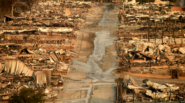 A man stands in the middle of the street at the Seminole Springs mobile home park in Malibu Lake after the Woolsey Fire roared through the community on November 10, 2018 in Malibu, California.