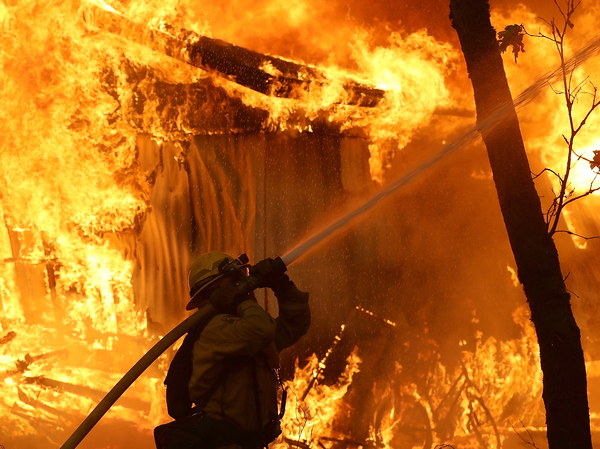 A Cal Fire firefighter monitors a burning home as the Camp Fire moves through the area on Nov. 9.