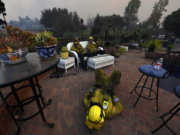 Los Angeles City firefighters Omar Velasquez (center), sleeps as Cory Darrigo (left), and Sam Quan rest in the backyard of home they were protecting after fighting the Woolsey Fire on Nov. 9, in Westlake Village, Calif.