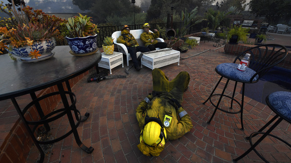 Los Angeles City firefighters Omar Velasquez, center, sleeps as Cory Darrigo, left, and Sam Quan rest in the backyard of home they were protecting after fighting the Woolsey Fire on November 9, 2018 in Westlake Village, Calif.