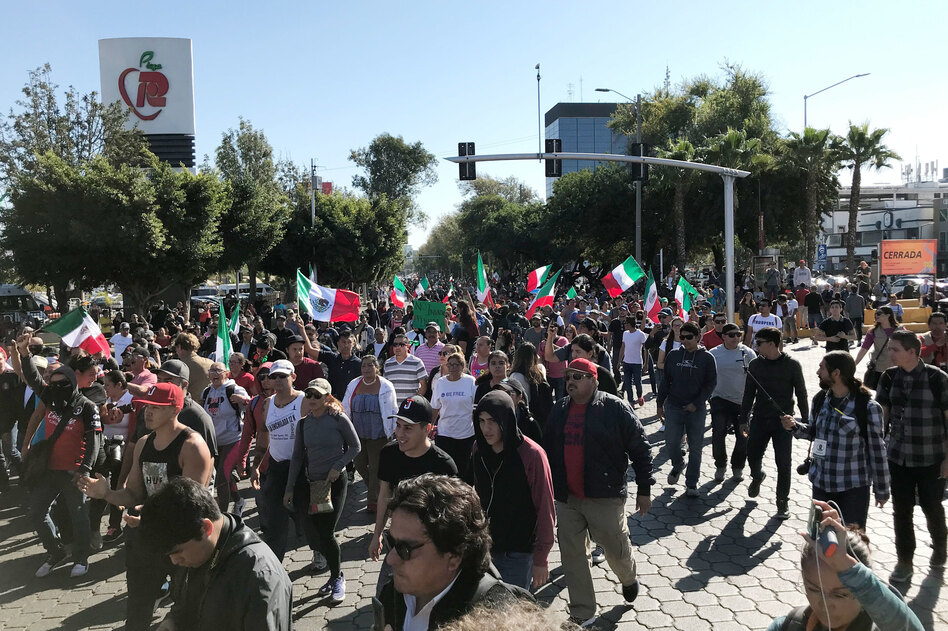 A few hundred people gathered in Tijuana's high-end Rio area on Sunday to protest against groups migrating from Central American countries. (James Fredrick for NPR)