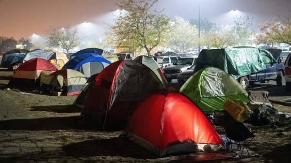 Evacuees retire to their tents for the night in a Walmart parking lot over the weekend in Chico, Calif. The deadliest fire on record in the state has left the living scrambling for answers.