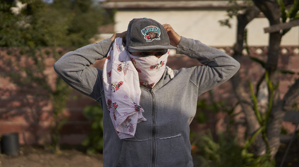 Gabriela, 32, a strawberry picker from Oaxaca, poses for a portrait at her home in Oxnard, Calif. on Nov. 18, 2018. Gabriela wears a bandana she used to cover her nose and mouth to avoid inhaling smoke while working in the fields during the Hill Fire.