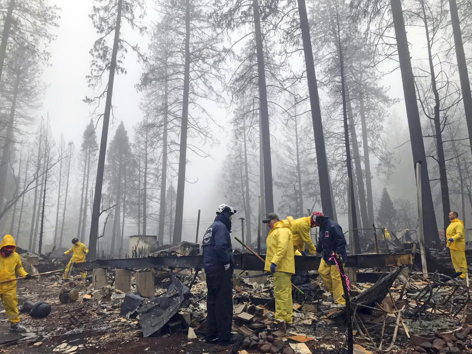 Volunteers search a mobile home park in Paradise, Calif. Government scientists predict wildfires like the one that struck this community will contribute to billions in losses for the U.S. economy. (Kathleen Ronayne/AP)