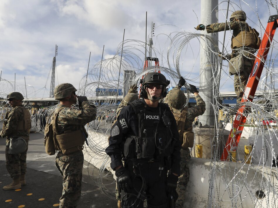 Troops set up concertina wire as a Customs and Border Protection agent stands guard on the U.S. side of the border with Mexico, on Thanksgiving Day. (Rodrigo Abd/AP)