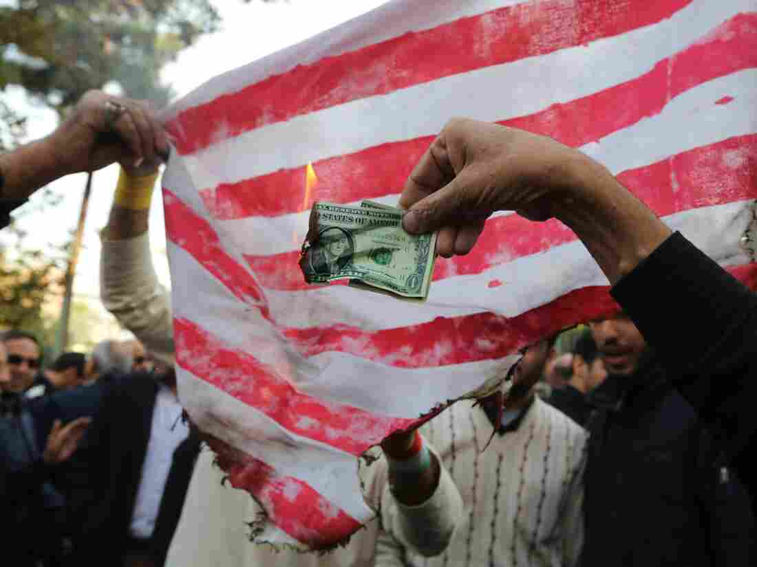 On the eve of renewed sanctions by Washington, Iranian protesters burn a dollar banknote and a US makeshift flag during a demonstration outside the former US embassy in the Iranian capital Tehran. (Photo by ATTA KENARE / AFP) (Photo credit should read ATTA KENARE/AFP/Getty Images)