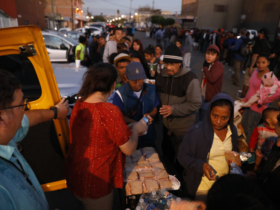 Well-wishers distribute food to migrants outside of a sports complex where more than 5,000 Central Americans are sheltering, in Tijuana, Mexico. President Trump wants the migrants to stay in Mexico while their asylum claims play out in U.S. immigration court. (Rebecca Blackwell/AP)
