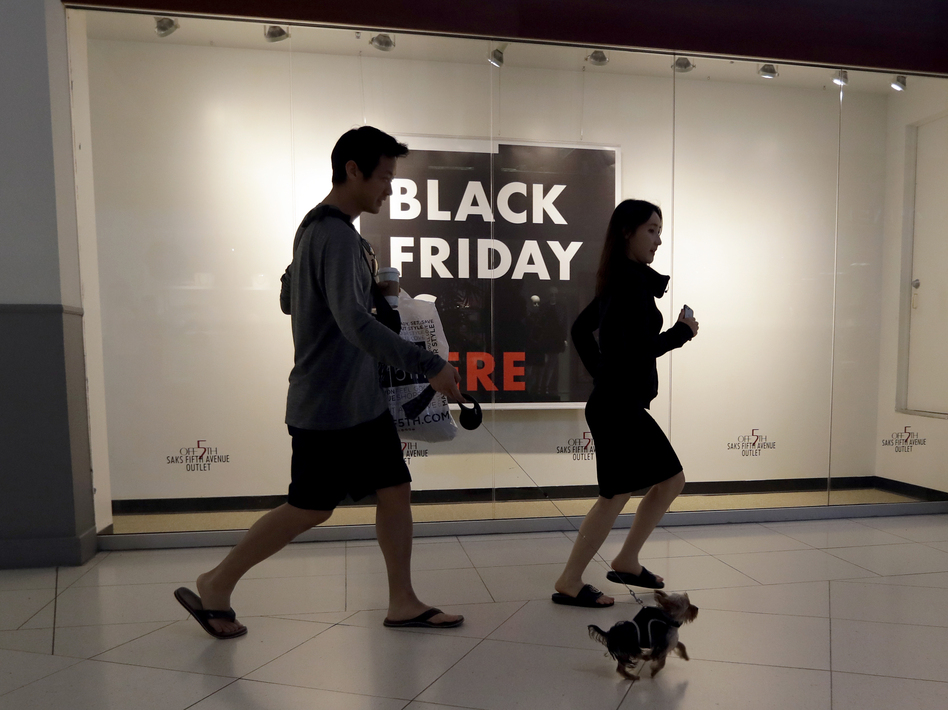 Shoppers walk past a Saks Fifth Avenue outlet store in Miami on Black Friday. Millennials have lower earnings, fewer assets and less wealth, a new Federal Reserve study says. (Lynne Sladky/AP)