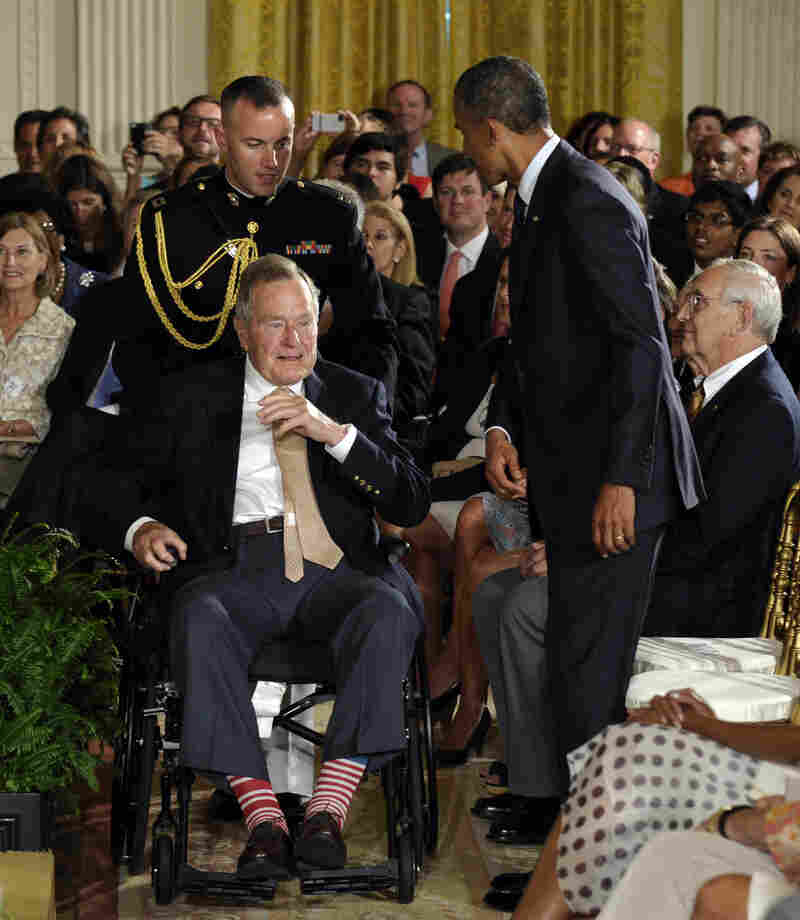 Bush is being rolled off the stage in red and white socks and sitting next to President Barack Obama after awarding the 5,000th Light Point of Light Award in the East Room of the White House on July 15, 2013