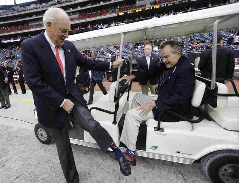 Owners of Houston Texans, Bob McNair (left) and Bush, show their socks before an NFL football game between the Houston Texans and the Jacksonville Jaguars on November 24, 2013 in Houston.