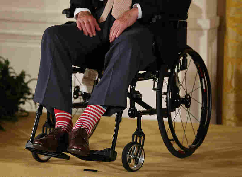 Bush wears red striped socks as he sits in a wheelchair during an event in the East Room at the White House on July 15, 2013.
