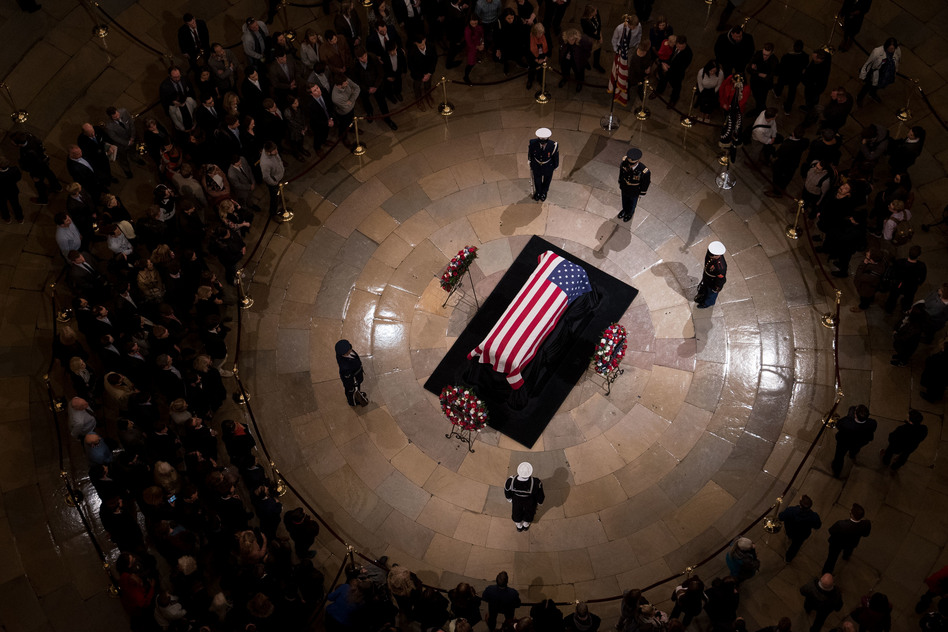 Members of the public view the casket containing former President George H.W. Bush's remains as he lies in state in the U.S. Capitol Rotunda on Monday night. (Cameron Pollack/NPR)