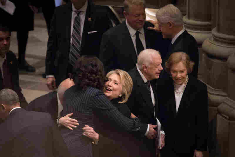 Former first ladies Michelle Obama and Hillary Clinton hug before the funeral Wednesday at Washington National Cathedral.
