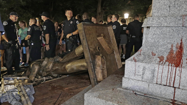 UNC-Chapel Hill students are unhappy with a university proposal to display a confederate statue in a new building. Police stand guard after the statue, known as Silent Sam, was toppled by protesters on campus in August.