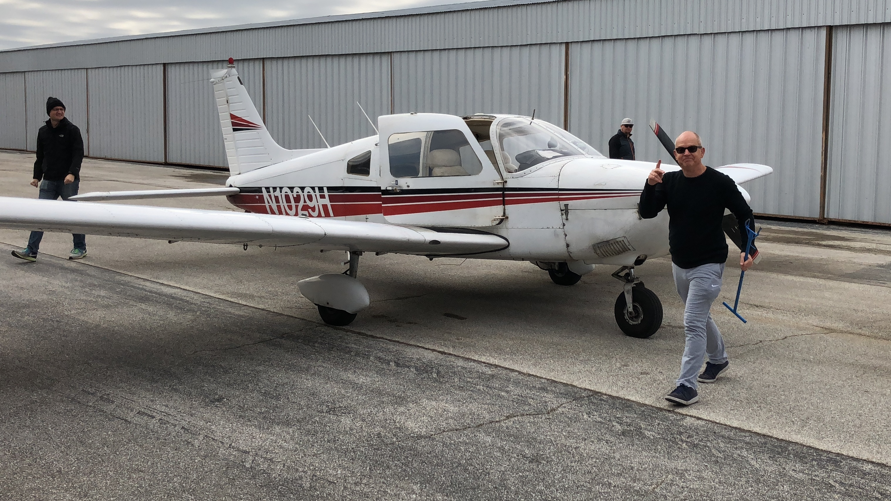 Jackson Busenbark carries a tow bar after towing his plane out of the aircraft hangar in preparation for a flight.