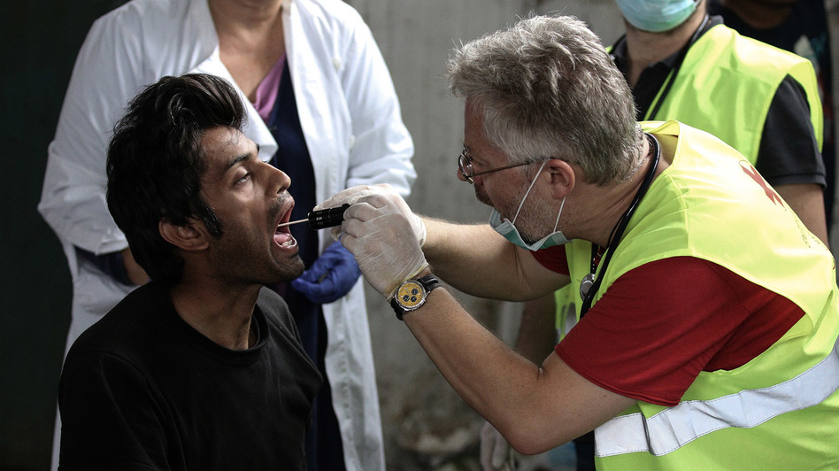 A migrant receives medical attention at a former paper factory in Greece that has been turned into a makeshift camp.