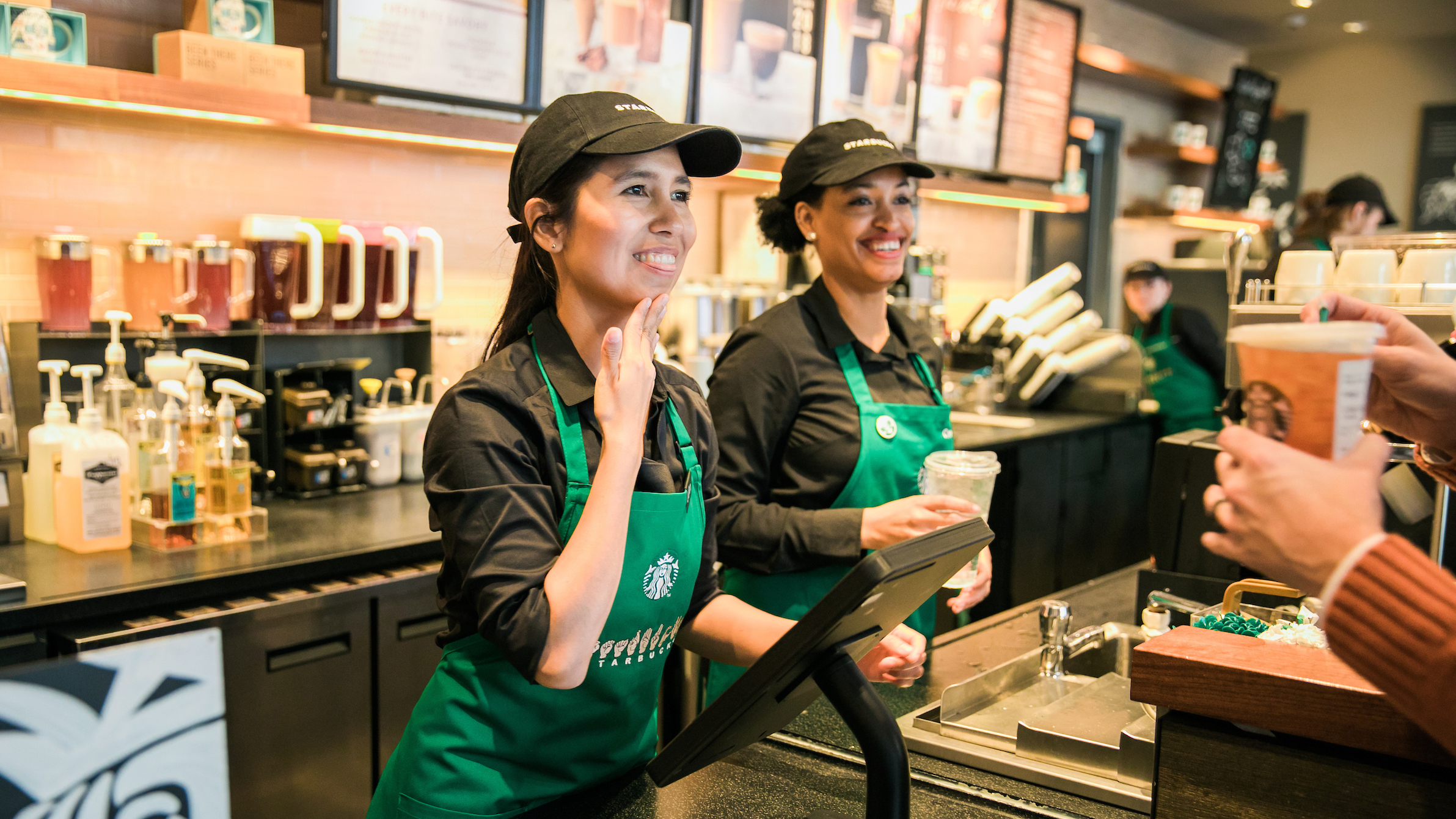 """A deaf barista signs """"thank you"""" after taking an order at the first U.S. Starbucks Signing Store."""