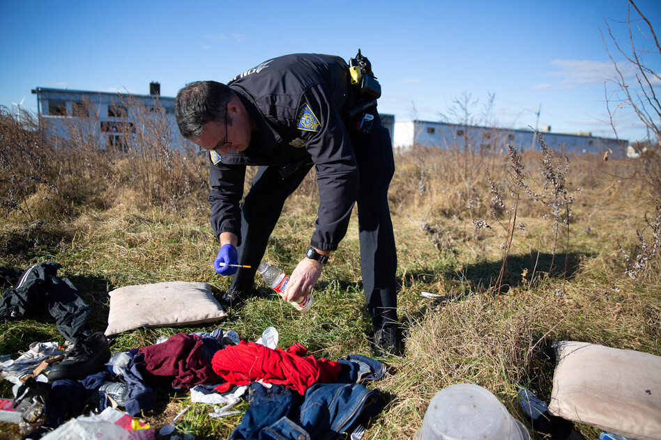 Officer Christian Bruckhart collects used needles from a vacant site in his patrol area in New Haven, Conn. (Ryan Caron King/Connecticut Public Radio)