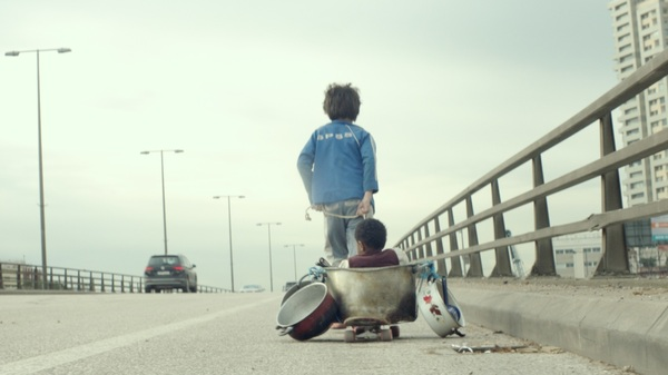 Zain (Zain Al Rafeea) pulls companion Yonas (Boluwatife Treasure Bankole) on a makeshift wagon in the movie Capernaum.