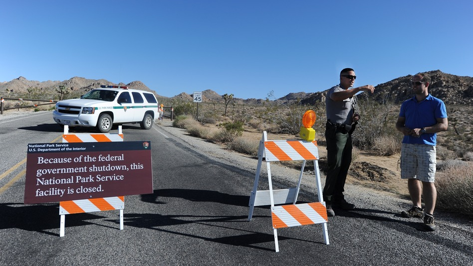 A U.S. park ranger gives a tourist suggestions of other nearby places to visit while Joshua Tree National Park was shut down in 2013. (Robyn Beck/AFP/Getty Images)