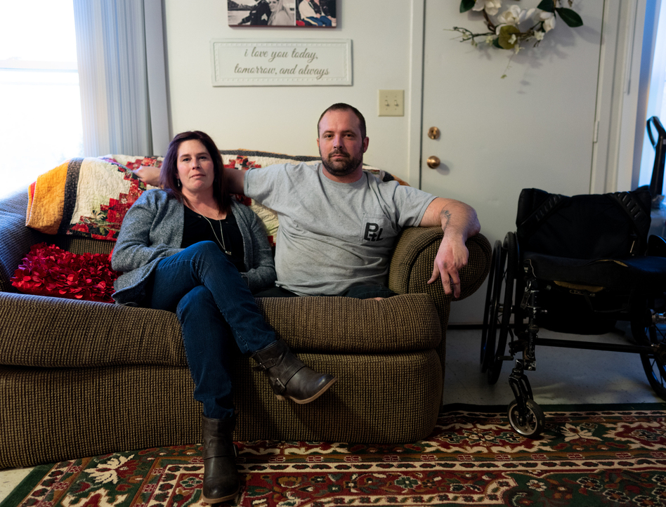 Ret. Sgt. Chris Kurtz and his wife Heather Kurtz pose for a portrait on the couch in their living room. (Erica Brechtelsbauer for NPR)