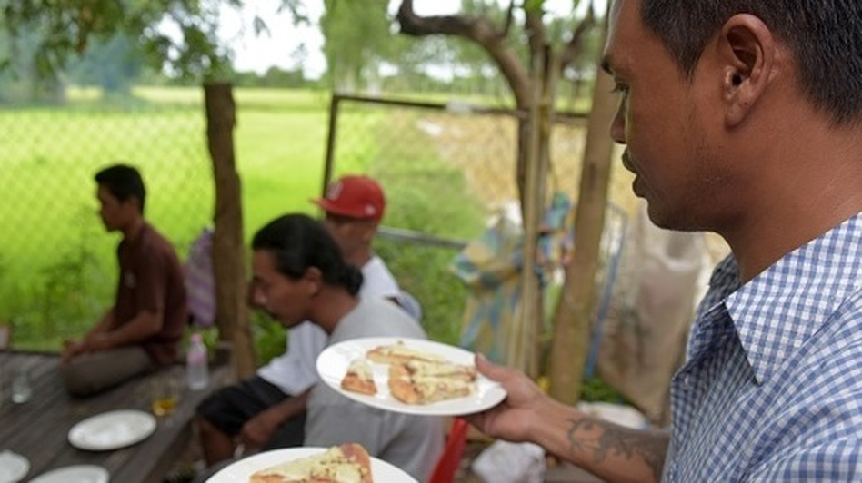Nheb Thai, a Cambodian refugee who was deported from the U.S., serves a meal to other deportees in Battambang last year. Cambodia has taken in 566 deportees since inking a 2002 pact with the U.S. that opened the door for hundreds with criminal records to be repatriated. (Tang Chhin Sothy /AFP/Getty Images)