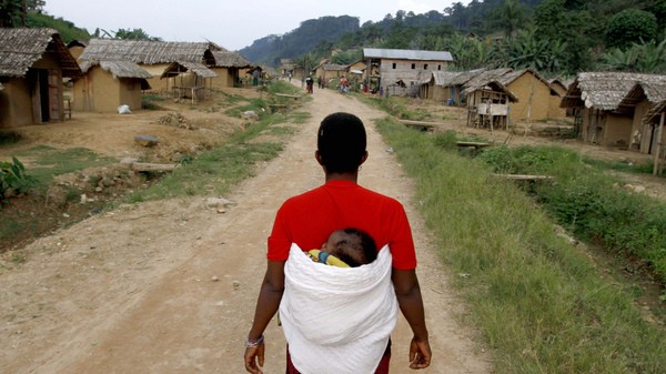 A woman walks down the main road in the village of Luvungi in the Democratic Republic of the Congo. In 2010, Hutu rebels and local militias raped more than 280 women and children as punishment for the villagers