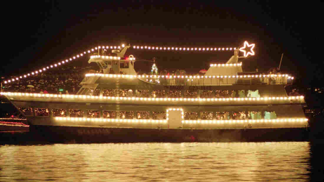 The small Argosy cruise ship Spirit of Seattle dresses up with Christmas lights and carries passengers on a Christmas caroling cruise around Lake Washington from Seattle.