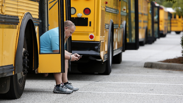 Jay McAbee, a bus driver with the Greenville, S.C., school district, waits by his bus in Charleston, S.C., in October of 2016, for word of when to start evacuating the city