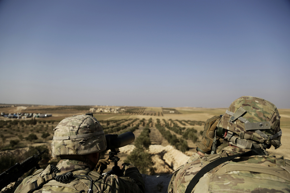 American troops look toward the border with Turkey from a small outpost near the town of Manbij, northern Syria, in February. (Susannah George/AP)