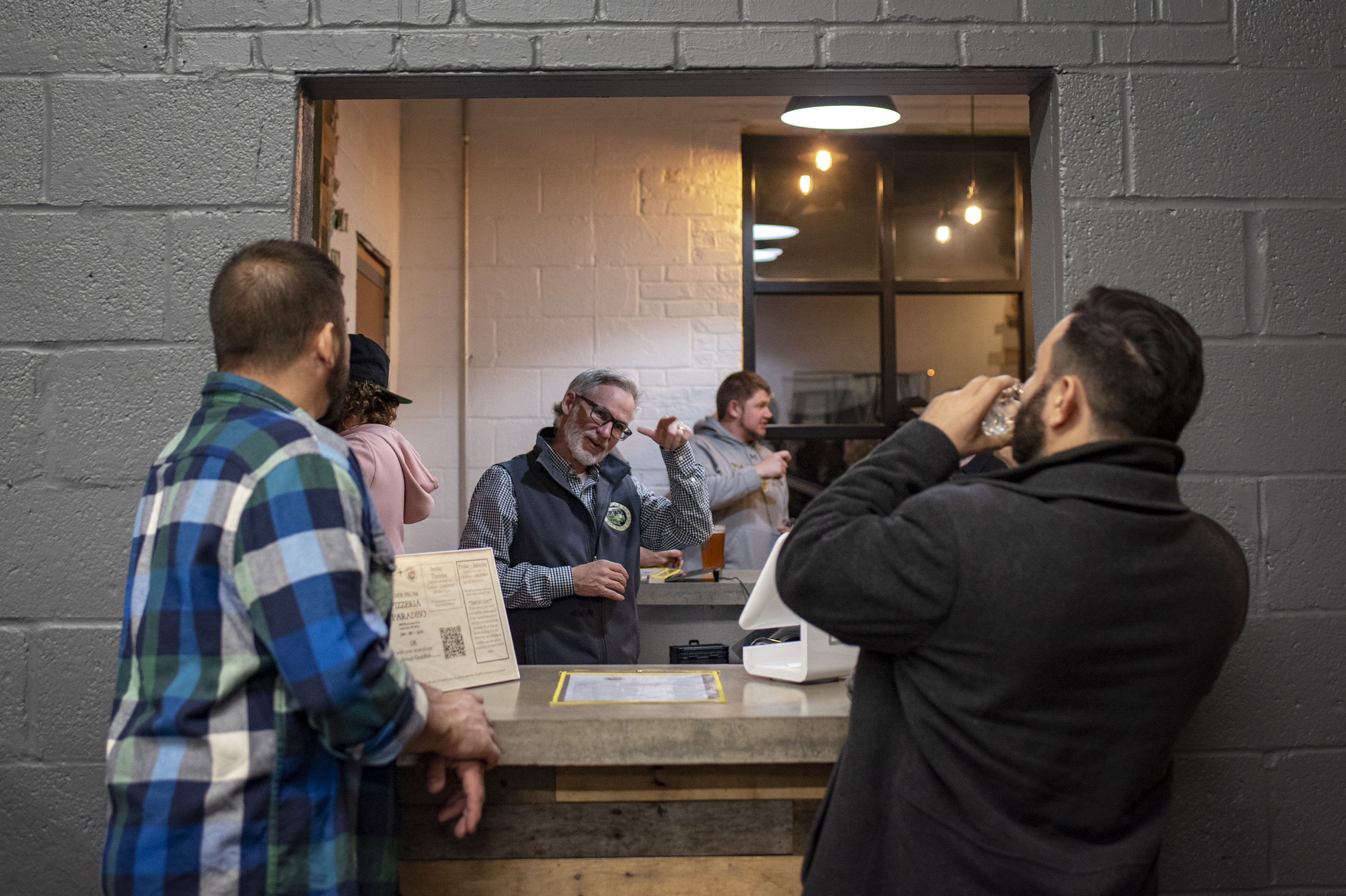 Co-founder Mark Burke signs with patrons at Streetcar 82 Brewing Co. in Hyattsville, Md. The brewery caters to deaf and hearing people.