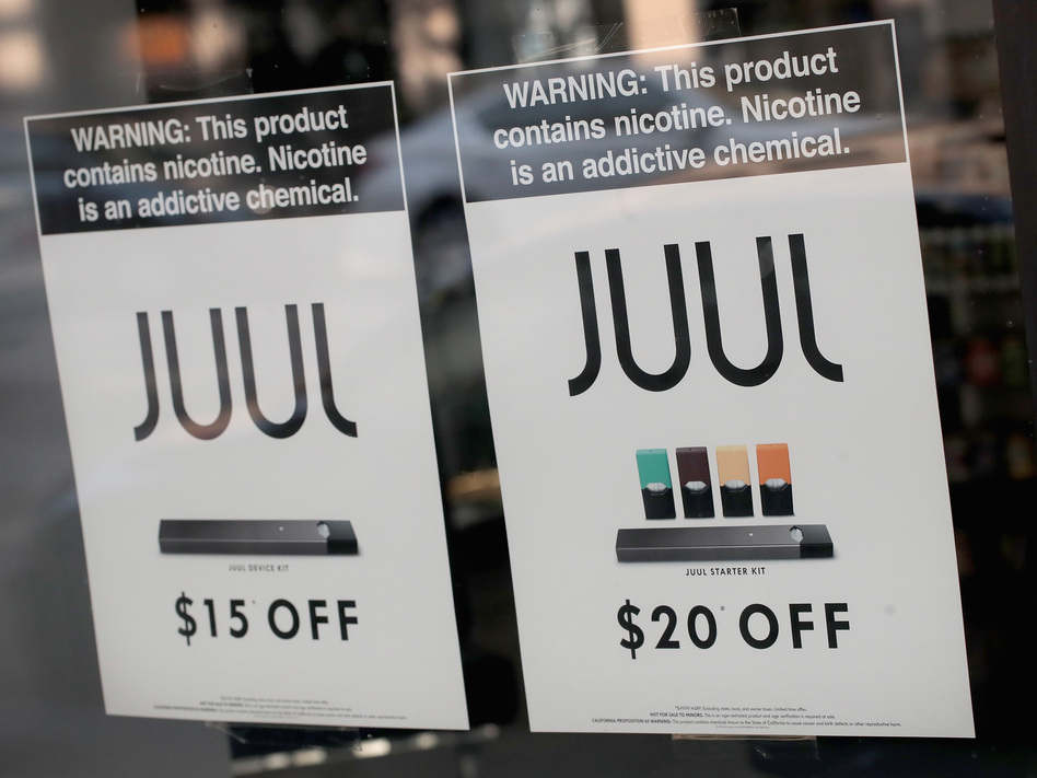 Signs in a Chicago shop window advertise e-cigarettes and pods from Juul in September. Altria, the parent company of Philip Morris, announced Thursday it would buy a 35 percent stake in the company. (Scott Olson/Getty Images)