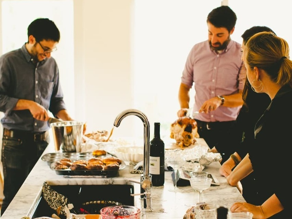 Michael Durand (left), husband of Kitchn Editor-In-Chief Faith Durand, and friend Chris Gardner (right) carve turkey while guests hang out in the Durands' kitchen, dirty dishes and all, at a recent party. (Kitchn/Rachel Joy Barehl)