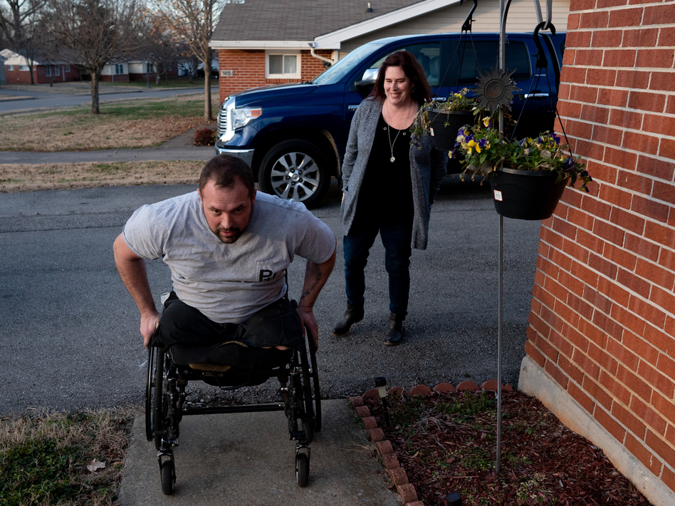 Retired Sgt. Chris Kurtz wheels himself up to his front door as his wife and caretaker, Heather Kurtz, follows behind. The Department of Veterans Affairs told him last summer that he no longer needs a caregiver. (Erica Brechtelsbauer for NPR)